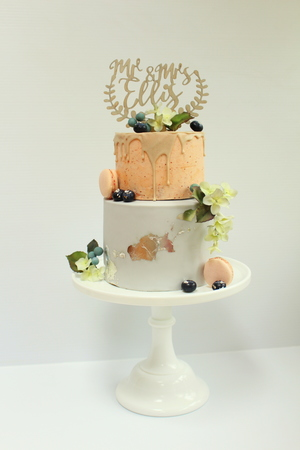 Informal wedding cake with two flavours (dark Belgian chocolate mud filled with peanut meringue buttercream and strawberry cake with fresh strawberry meringue buttercream and strawberry chocolate drip) adorned with handmade sugar flowers and berries