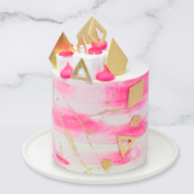 "The ""Geometric, Gold & Cerise Watercolour"" Cake is a buttercream iced cake. The single tier is 6″ deep and 2 tier options are 10″ deep. This cake also includes chocolate gems, marshmallows and the geometrics shapes are also edible. A name plaque can be added to the front of the cake."