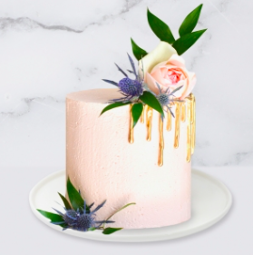 The Drip & Flower Cake is a buttercream iced cake. The single tier is 6″ deep and 2 tier options are 10″ deep. A name plaque can be added to the front of the cake.  The hand painted gold drip is edible. The flowers and greenery are fresh and not edible. Note: The colour and size of the flowers and greenery may vary due to availability.